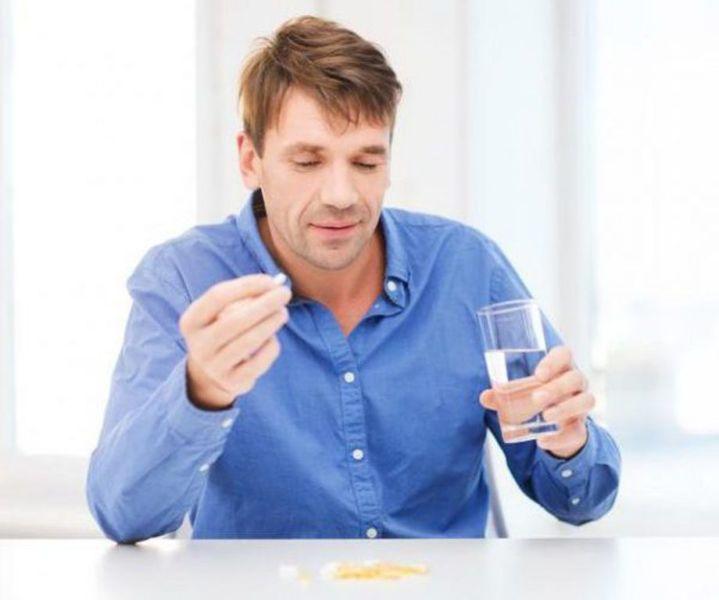 Мужчина пьет таблетку